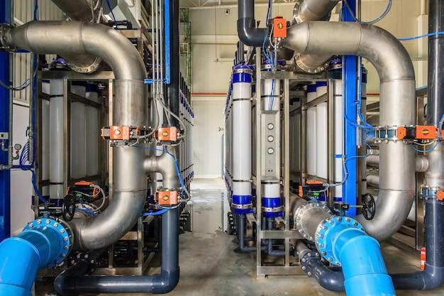 Grand traitement des eaux industrielles et chaufferie. tuyaux en acier brillant et pompes bleues Photo Premium