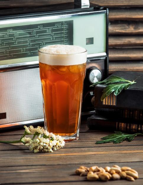 Un grand verre de bière et de cacahuètes salées. Photo gratuit