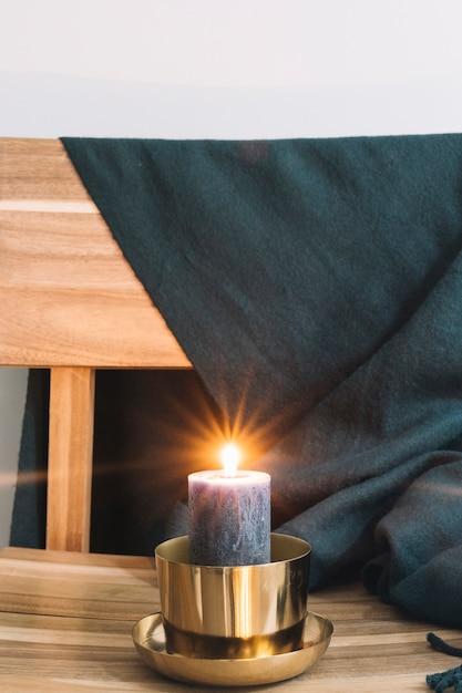 Grande bougie au chandelier sur une chaise Photo gratuit