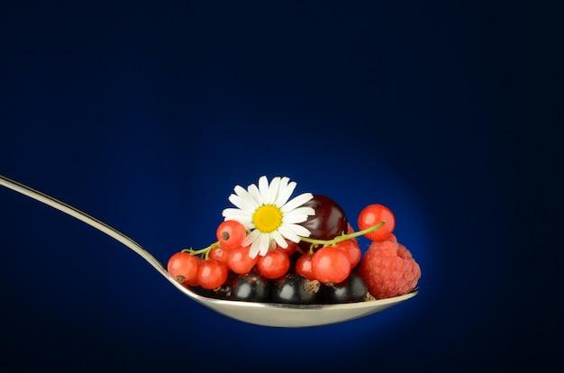 Une grande cuillère pleine de baies sauvages juteuses de groseille rouge, cerise, framboise, cassis et framboise, avec des feuilles vertes et une fleur de camomille sur un bleu. fraîcheur et été dans une cuillère. Photo Premium