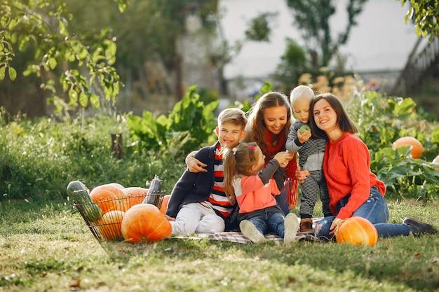 Grande famille assise sur un jardin près de nombreuses citrouilles Photo gratuit