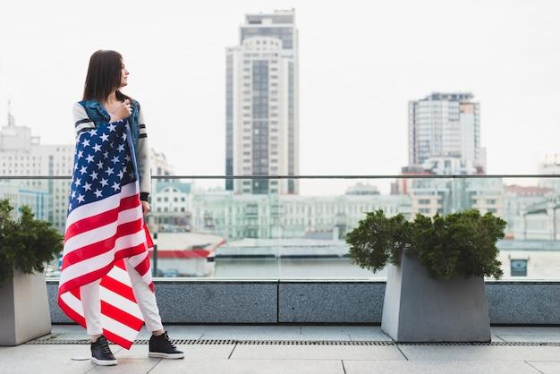 Grande femme sur un balcon enveloppé dans un drapeau américain Photo gratuit
