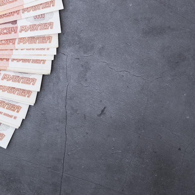 Grande pile de billets de banque russes de cinq mille roubles, reposant sur un ciment gris. Photo Premium
