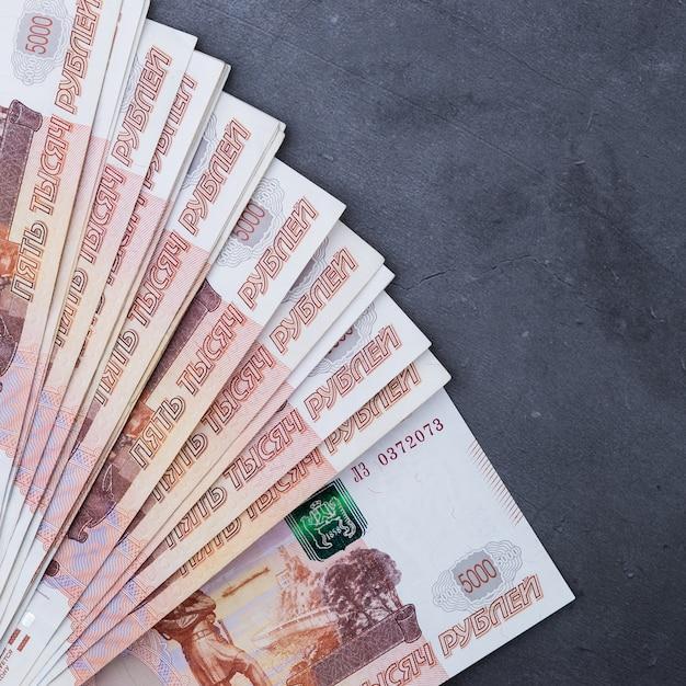 Grande pile de billets de banque russes de cinq mille roubles se trouvant sur du ciment gris Photo Premium