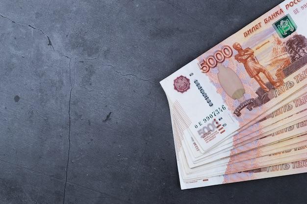 Grande pile de billets de banque russes de cinq mille roubles se trouvant sur du ciment gris. Photo Premium