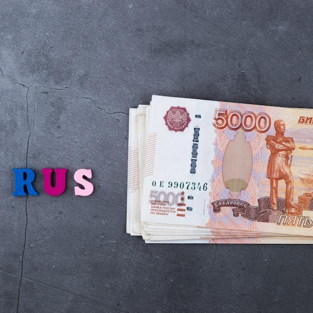 Grande pile de billets de banque russes de cinq mille roubles se trouvant sur un fond gris Photo Premium