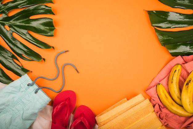 Grande Plante Verte Feuilles Près Des Bananes Et Des Vêtements D'été Photo gratuit