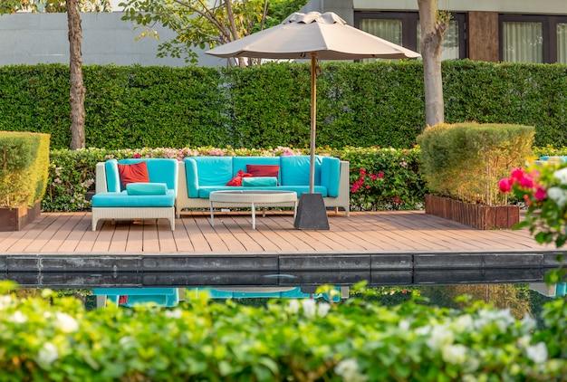 Grande terrasse avec mobilier en rotin dans le jardin avec parasol. Photo Premium