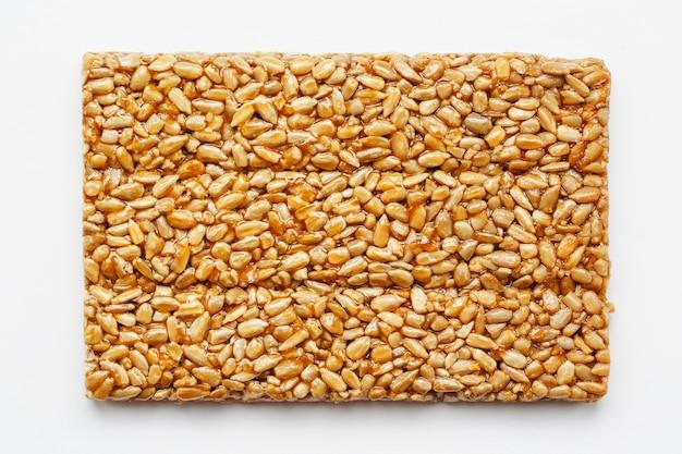 Une grande tuile dorée de graines de tournesol, une barre dans une mélasse douce. kozinaki bonbons utiles et savoureux de l'est Photo Premium