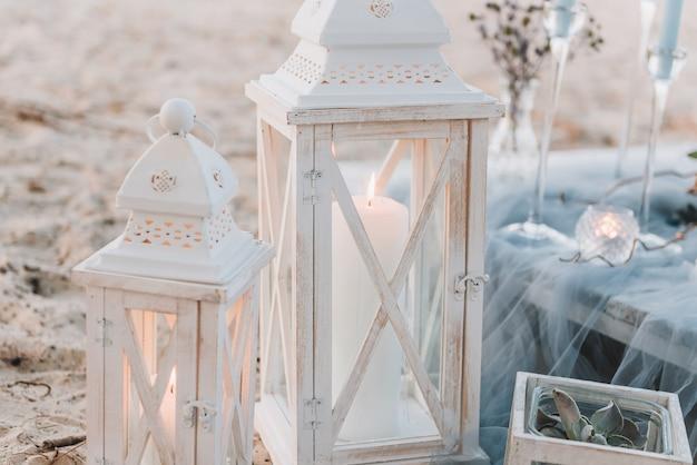 Grandes bougies à côté d'une élégante table en pastels bleus pour un mariage à la plage Photo Premium