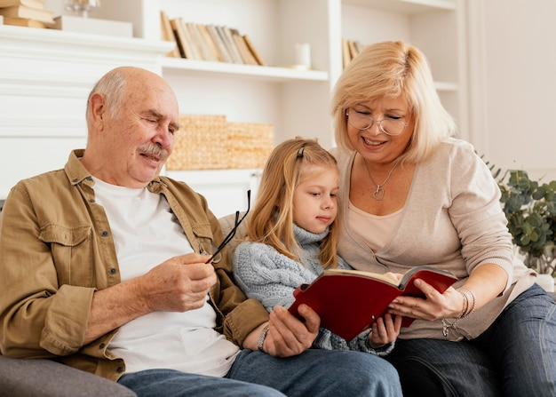 Grands-parents De Tir Moyen Lisant à L'enfant Photo Premium