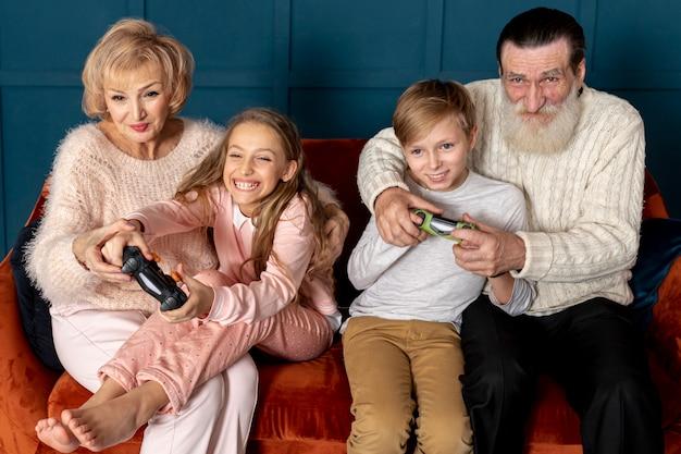 Grands-parents Vue De Face Jouant à Des Jeux Vidéo Avec Leurs Petits-enfants Photo gratuit