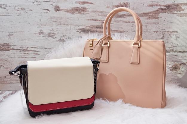 Grands Sacs Beige Et Blanc-rouge Sur Une Fourrure Artificielle Blanche. Concept à La Mode Photo Premium