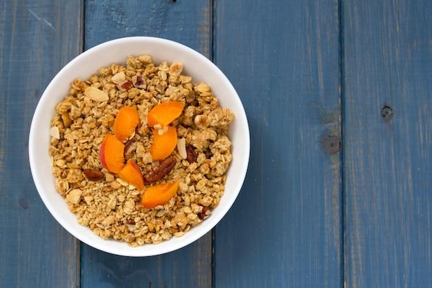 Granola aux fruits et noix dans un bol blanc sur une surface en bois bleue Photo Premium