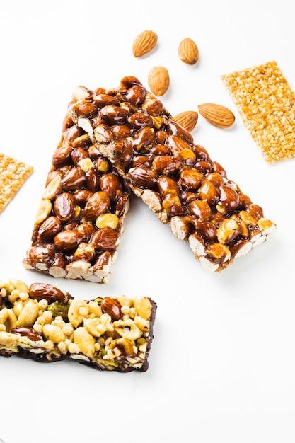 Granola; barres de graines de sésame et d'amandes sur fond blanc Photo gratuit
