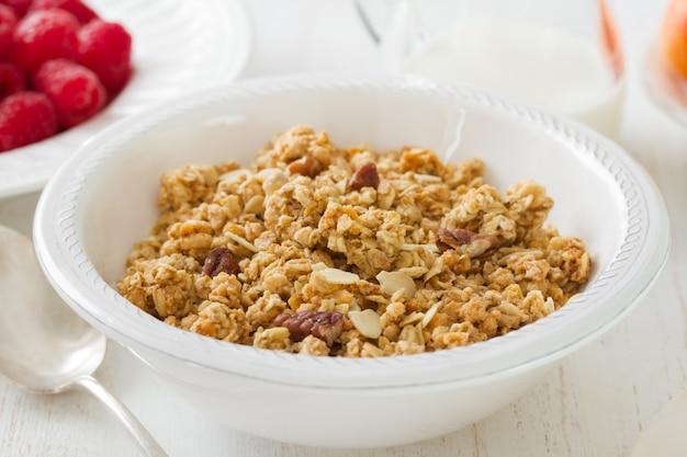 Granola dans un bol blanc avec du lait et des fruits sur une surface en bois blanche Photo Premium