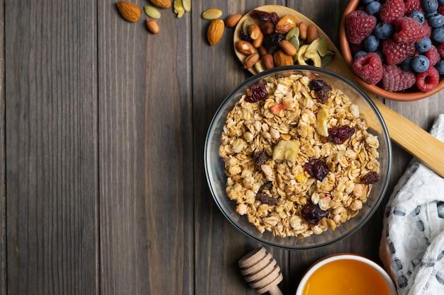Granola Maison Saine Avec Des Noix, Du Miel Et Des Baies Dans Un Bol En Verre. Surélevé à Plat Photo Premium