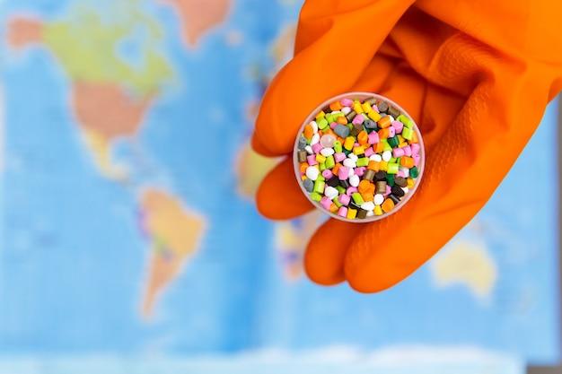 Granulés De Plastique Dans Les Mains Avec Des Gants Orange Sur Le Fond De La Carte Du Monde Photo Premium