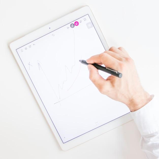 Graphique de dessin à la main de l'homme d'affaires avec stylet sur l'écran de la tablette numérique graphique Photo gratuit