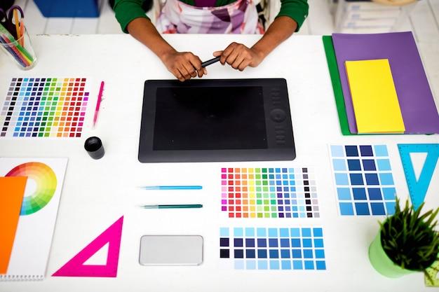 Graphiste au bureau avec des outils Photo gratuit
