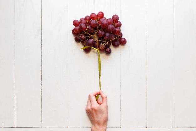 Grappe de raisin attachée avec un ruban dans la main d'une femme Photo Premium