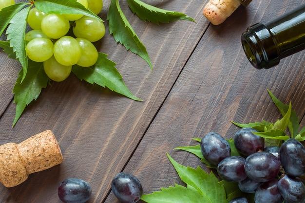 Grappe de raisin rouge et blanc, bouteille de vin et de liège sur fond de table en bois Photo Premium
