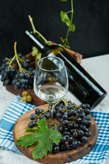 Une Grappe De Raisin Avec Un Verre De Vin Et Une Bouteille Sur Table Blanche Avec Nappe Bleue Photo gratuit