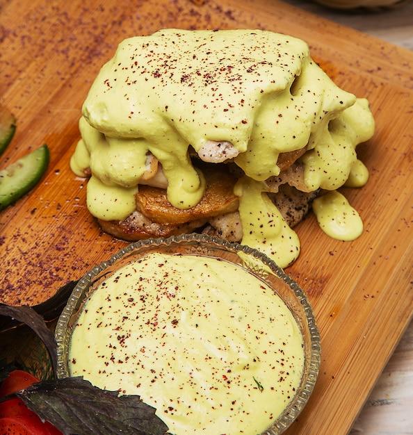 Gratin de poitrine de poulet et pommes de terre avec vinaigrette au fromage fondu au concombre sur planche de bois. Photo gratuit