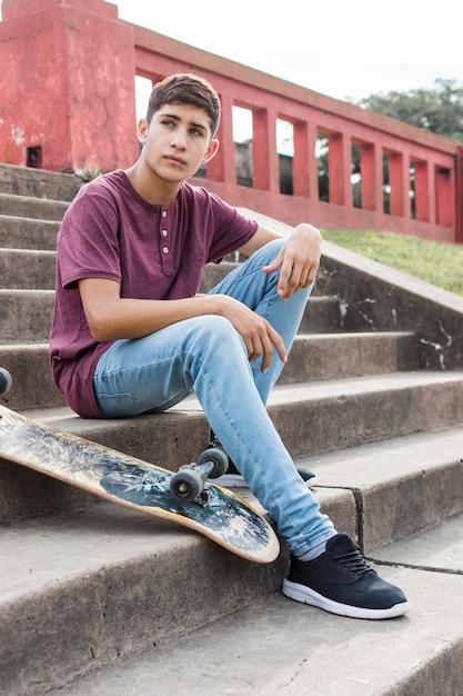 Grave, adolescent, séance, escaliers, à, skateboard, regarder loin Photo gratuit