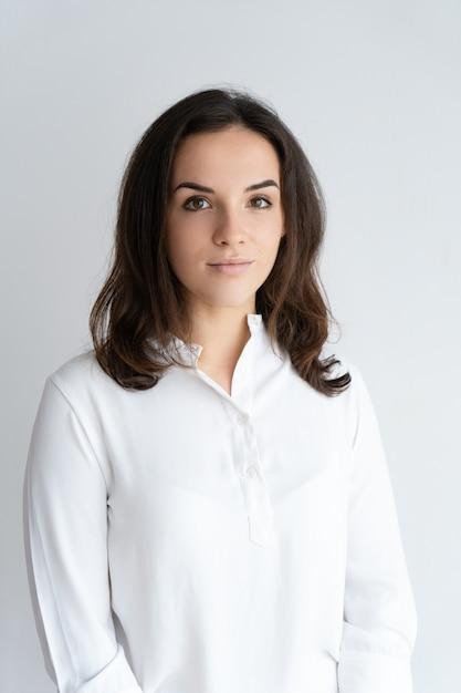Grave belle jeune femme regardant la caméra. dame en chemise blanche et posant. Photo gratuit