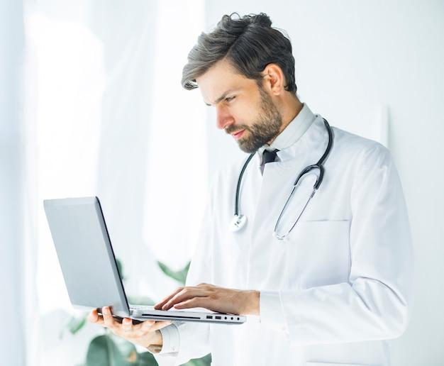 Grave jeune docteur naviguant sur un ordinateur portable Photo gratuit