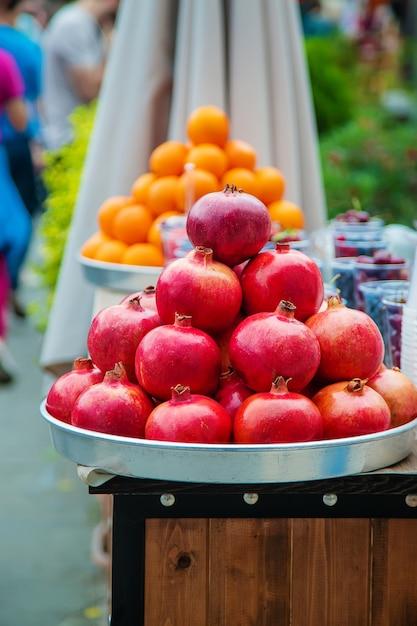 Les grenades et les oranges sont vendues sur le marché. Photo Premium