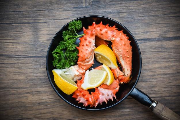 Griffes de crabe cuites sur un plat avec des fruits de mer du crabe royal d'alaska sur la table à manger Photo Premium