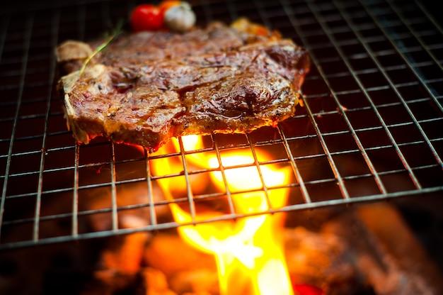 Griller t bone steak sur la grille flamboyante Photo Premium