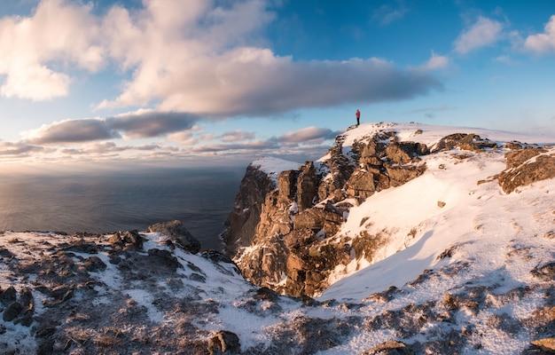 Grimpeur debout sur le sommet d'une montagne rocheuse en hiver au coucher du soleil Photo Premium