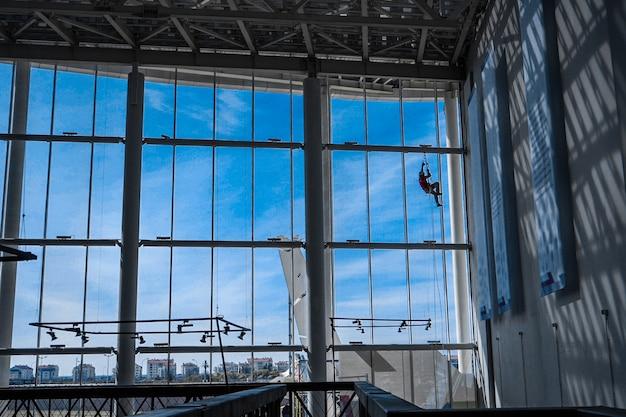 Grimpeur industriel est suspendu à des cordes à l'intérieur du bâtiment Photo Premium