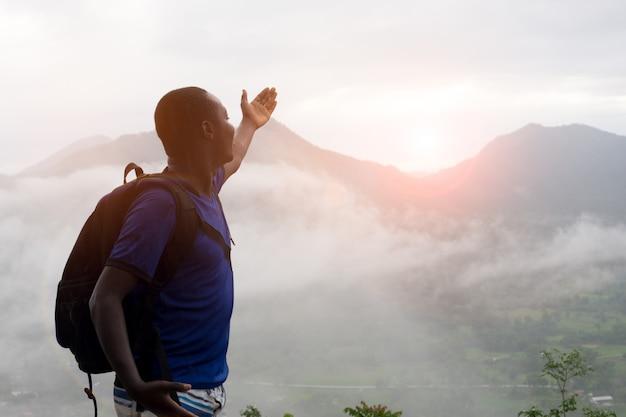 Grimpeurs africains assis au sommet de la colline couverte de brouillard. Photo Premium