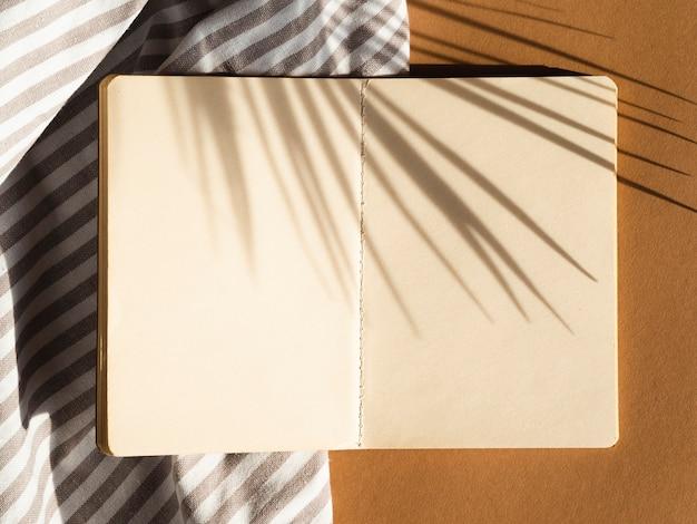 Gris et blanc dépouillé vierge sur fond beige avec ombre de feuilles de palmier Photo gratuit