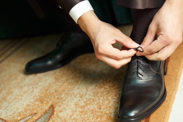 Groom robes et lie les chaussures Photo Premium