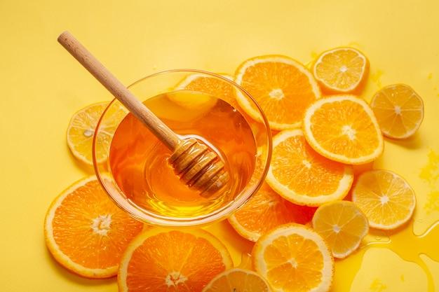 Gros bol de miel avec des tranches d'orange Photo gratuit