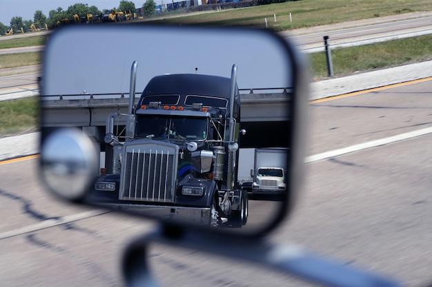 Un gros camion bleu dans le rétroviseur du véhicule Photo Premium