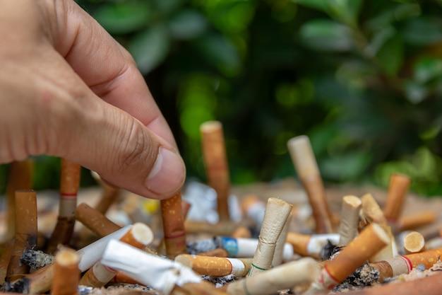 Gros cigarettes homme personne main pour fumer se tenir dans la zone fumeur. Photo Premium