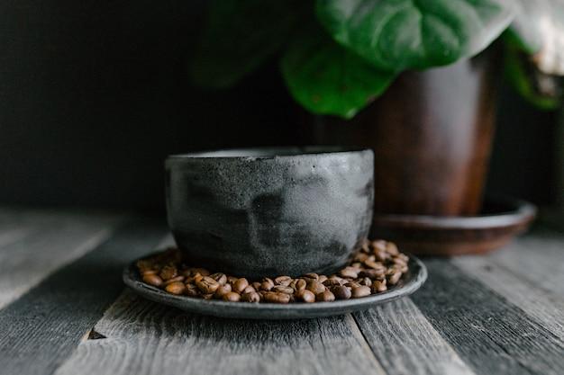 Gros Coup De Grains De Café Sur Une Plaque D'argile Sur Une Table En Bois Photo gratuit
