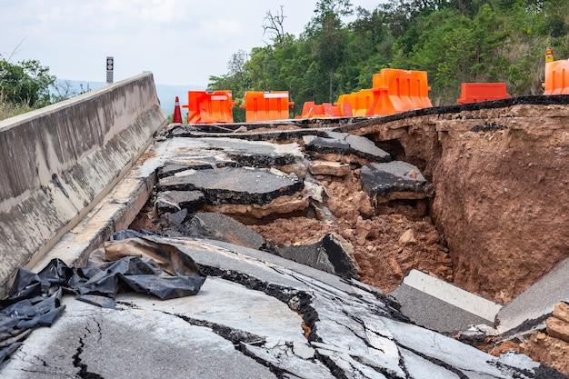 Gros dégâts de la route goudronnée sur le flanc de la colline causant de fortes pluies et de la terre glissante Photo Premium