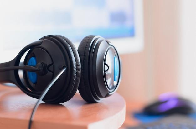 De gros écouteurs noirs se trouvent sur le bureau en bois du son Photo Premium