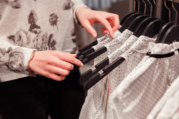 Gros femme les mains sur des cintres dans un magasin à la recherche d'une taille appropriée. Photo Premium