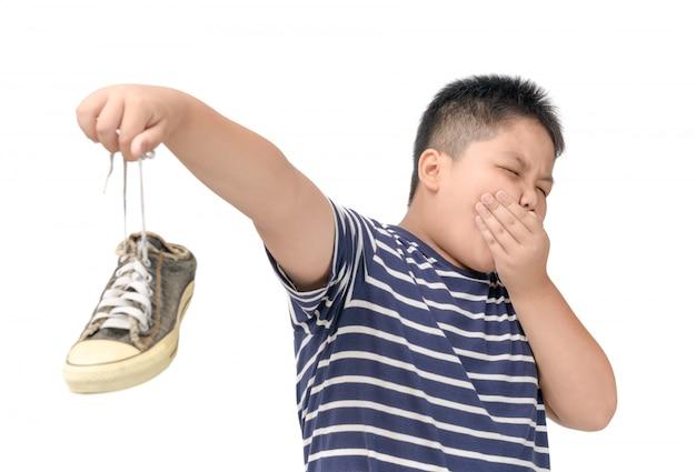 Gros garçon dégoûté tenant une paire de chaussures malodorantes Photo Premium
