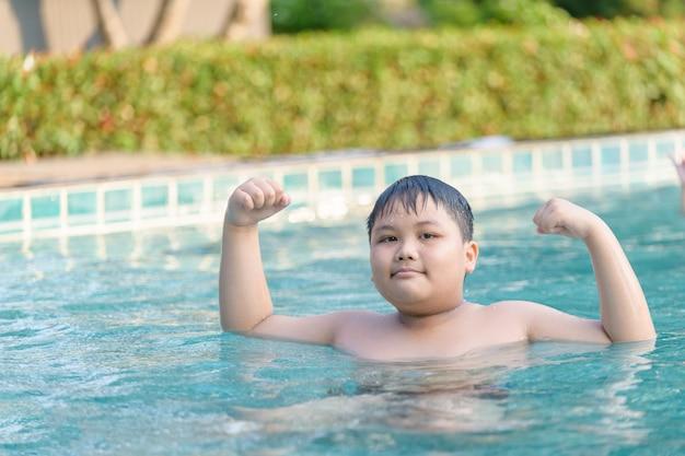 Gros garçon obèse montre le muscle dans la piscine Photo Premium