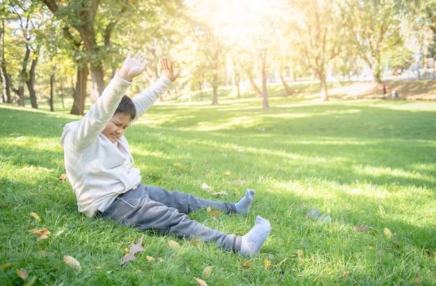 Gros garçon s'étirer dans parc Photo Premium