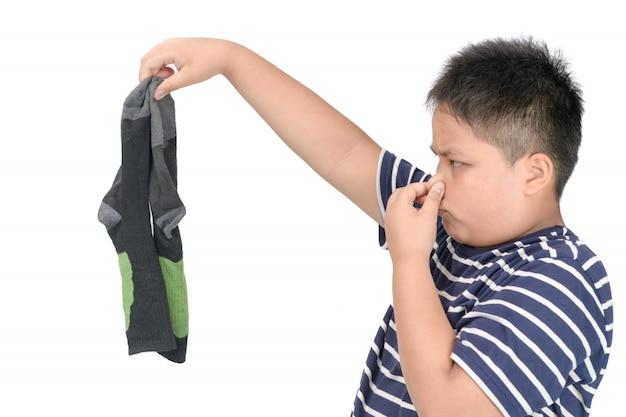 Gros garçon tenant des chaussettes de football puantes sales isolées Photo Premium